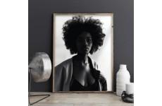 Plakat z czarnoskórą kobietą na tle ciemnej ściany